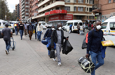 assengers wearing masks walk to a taxi rank as residents of a number of African countries where coronavirus is spreading